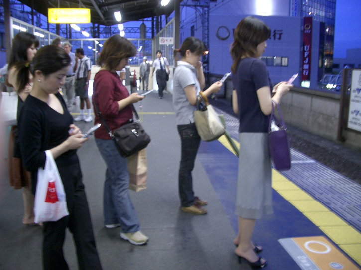 people using smartphones in public